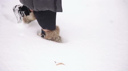 goes : A girl in fur warm winter boots walks through the snow in the park, close-up.