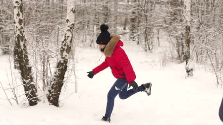 throws : Joyful girl throwing snow. Young Couple throwing a snowballs outdoors. Laughing People having fun in winter park. Slow motion. Winter activities. Stock Footage