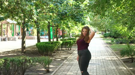 xxl : Uncomplexed young girl overweight posing in the Park in the summer among the green trees. Plus size model. Girl XXL.