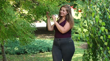 nagy : A young girl with excess weight walks in a park among green trees. Plus size model. Stock mozgókép
