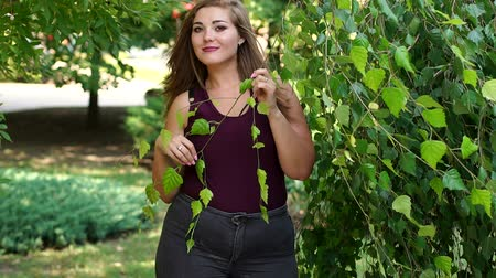 xxl : A young, relaxed girl with excess weight walks in the park in the summer. Portrait of a sexy fat girl against a background of green trees.