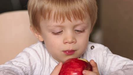 high calories : Close-up of a small blond boy eating a red apple sitting at a table at home, high resolution. Cute little child is biting red apple while sitting at table. Stock Footage