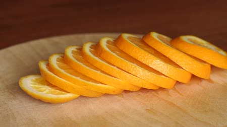 segmento : Sliced ripe juicy fruit oranges on a wooden table, close-up. Abstract background with citrus-fruit of orange slices. Close-up. Sliced orange background. Stock Footage