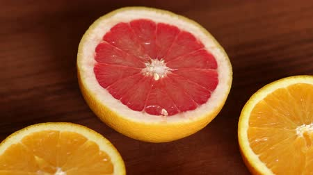 segmento : Four halves of juicy orange and grapefruit on a wooden brown background. Sliced oranges and grapefruit on wooden table. Close-up. Slow motion. Stock Footage