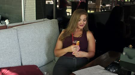 xxl : A pretty fat girl is sitting in a trendy cafe with a bright cocktail. A girl with excess weight drinks lemonade in a street cafe.