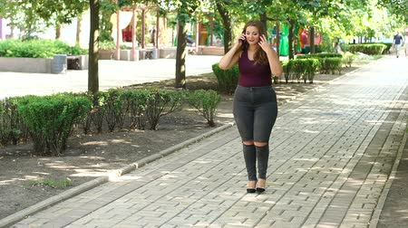 xxl : A teenage girl with excess weight walks in the green park along the alley and talks on the phone.