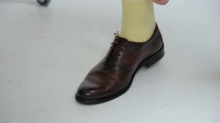 тянуть : Close-up of a male businessman adjusting socks under his trousers, tying shoelaces.
