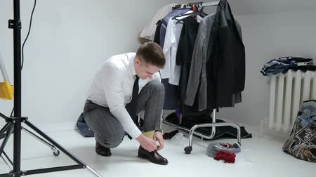 cadarço : A young man tying elegant shoes in the dressing room. Businessman or groom tied a shoelace on his black shoes. Vídeos