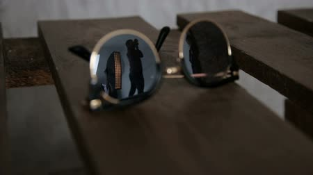 хром : Close-up of a male photographer is reflected in sunglasses in the Studio while working. Стоковые видеозаписи