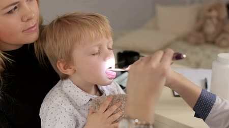hrdlo : A girl doctor examines the throat and mouth to a small child with a flashlight and a spatula, a small boy is sitting on his mothers arms and holding a teddy bear. Pediatrics. Dostupné videozáznamy