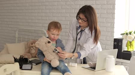 плюшевый мишка : Doctor and boy patient examining teddy bear in Hospital. A pediatrician woman plays with a small boy patient with a stethoscope and a teddy bear.