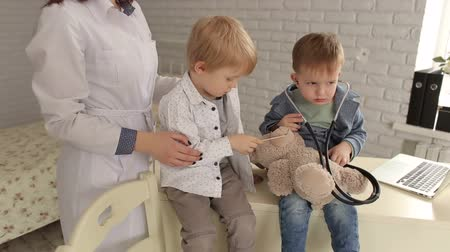 puericultura : Doctor and two boys patient examining teddy bear in Hospital. A pediatrician woman plays with a two small boy patient with a stethoscope and a teddy bear. Stock Footage