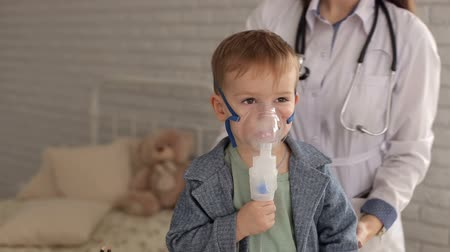 inhalacja : Close-up portrait of a little boy with an inhalation mask from a nebulizer, next to him stands a female doctor. Wideo