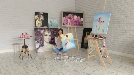портфель : Talented girl artist sitting on the floor in the Studio to paint among many of his paintings, portrait. Portrait of a young talented girl in the drawing Studio among the many paintings. Стоковые видеозаписи