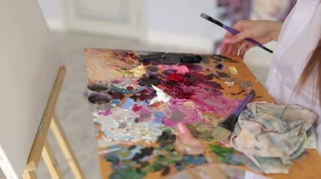 oilpaint : Close-up of the girl holding a large palette of paints and brushes for drawing. Art, hobby, teaching drawing.