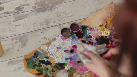 oilpaint : Close-up of a girl washes a brush to paint in a small container with water. Close-up of a palette for paints, a paintbrush and a dirty rag. Art.