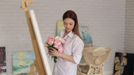piwonie : Portrait of a beautiful girl with a bouquet of pink peonies in the drawing Studio. A talented thoughtful girl stands in front of an easel with a canvas with a bouquet of flowers.