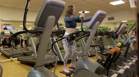 might : Sport girl on orbitrek in the gym. Sport girl run on orbitrek in a gym, body fitness- concept. Hard cardio workout.