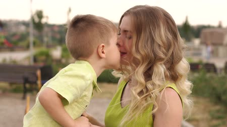 anne : Close-up of a little cute boy kissing his beloved mommy in the park in the summer. Portrait of a happy mother and her little son in a playground. Stok Video