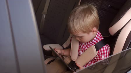 fasten : A small blonde boy of five years is sitting in a car seat in a car and playing a tablet. Slow motion. Close-up.