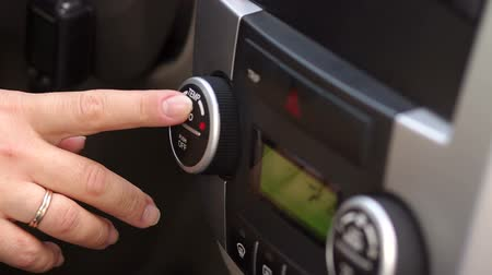 samochód : The girl includes the climate control in the car, close-up. Close-up of hand pressing buttons in the car multimedia panel.