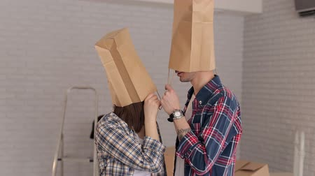 caráter : Happy newlyweds have fun in their new apartment with cardboard bags on their heads. Playful couple with boxes on heads, housewarming. Stock Footage