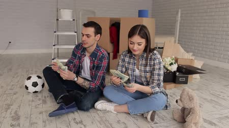 belongings : A young couple sits on the floor in their new apartment among boxes and count the money.