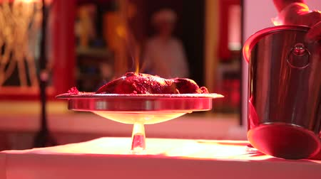 calor : Cook sets fire to the chicken in the restaurant. The signature dish. Close-up. Cooking chicken on the fire. Stock Footage