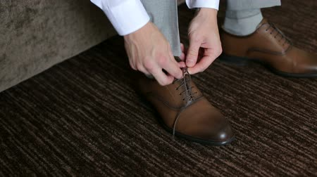casual wear businessman : Man ties up shoelaces on brown leather shoes, close-up.