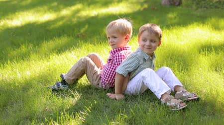 into the camera : Two cheerful little boys of 4 years old are sitting back to back in the park on the grass. Two young children relax in the summer in nature.
