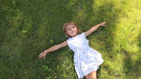 outside view : Little cute girl in white dress lying on green grass in Sunny Park in hot weather. Unusual little girl with different eye color in the Park, portrait. The view from the top.