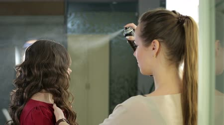 kıvırcık saçlar : Woman stylist applies hairspray on hairdo in beauty salon. Female holds brown hair in hands and spray neatly with lacquer for fix hair on fashionable hairstyle.