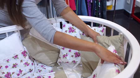 cradle : A pregnant girl chooses a baby cot in the childrens clothing store, close-up. Pregnant woman choosing Baby clothing in baby and maternity shop. Stock Footage