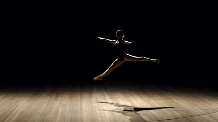 trained : Girl ballerina doing horizontal twine in the air on stage on black background, slow motion. Stock Footage