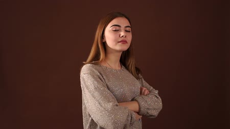 dobrado : Portrait of serious focused girl with arms crossed on brown background, slow motion.