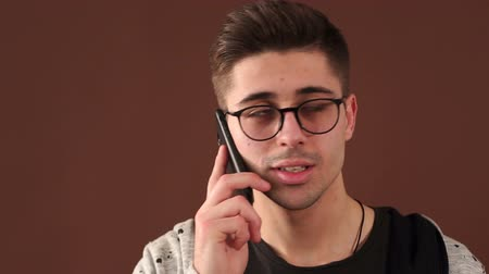 desperate student : Close-up portrait of a young guy with glasses and sports clothes screaming at the phone. Angry young boy screams to the mobile phone. Young caucasian man angry, frustrated and furious with his phone.