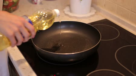 induction cooker : Chef pouring vegetable oil to the pan. Pouring vegetable oil into frying pan. Chef pouring oil into the frying pan for cooking.