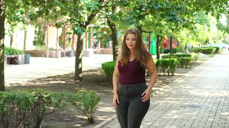 nagy : Girl model overweight posing in a Sunny summer city Park. Fat young teen girl in the Park. Slow motion.