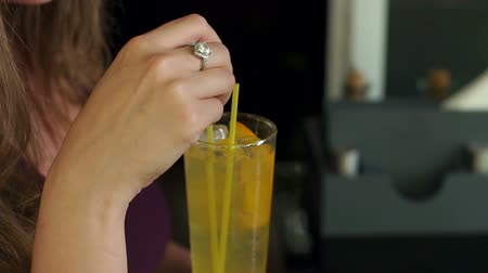 xxl : Close-up of a glass of lemonade in the hand of a girl in a cafe. Slow motion. Summer cool drinks. Stock Footage
