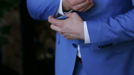 nákrčník : Successful man in the blue suit straightens his sleeves, close-up. Morning of a successful businessman.