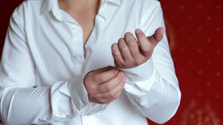 gentleman : Close-up of a successful businessman fastens buttons on the sleeves of his white shirt. The morning of the businessman.