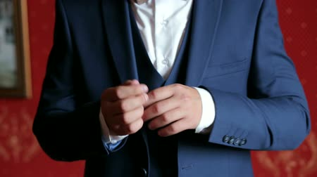 nákrčník : Successful man in the blue suit straightens his sleeves, close-up. Close-up of a successful businessman straightens the sleeves of his jacket and shirt dressing in the morning.