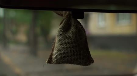 dezodorant : Air freshener in the form of pouch hanging on back view mirror inside car, in the background blurred image of working wipers in the rain and the silhouette of the car with the headlights.