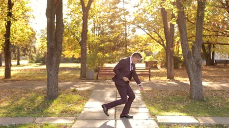 mellow autumn : A successful happy businessman in a suit dancing in the autumn Park enjoying success in business or victory. Winning dance businessman in the autumn Park at sunset. Stock Footage
