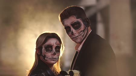 muertos : Couple with dark skull makeup on the background of burning fire and smoke. Halloween face art. Halloween concept. Zombie. Silhouette. Slow motion.