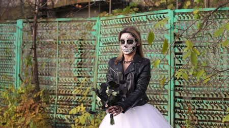 маска : A creepy bride with a bouquet of black flowers and make-up in the form of a skull stands against a rusty green fence. Woman dressed in costume cosplay horror dead bride or ghost on Halloween festival.
