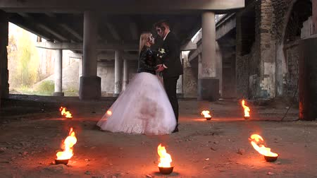 zombi : Couple in bridal gowns with halloween makeup in the shape of a skull stand embracing under an old abandoned bridge, with fire burning around them. Halloween.