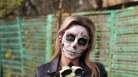 маска : Portrait of a scary girl with make-up on a halloween in the form of a skull with a bouquet of black flowers. Slow motion. Woman in dress and makeup for halloween in the forest. Стоковые видеозаписи
