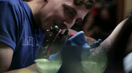 creator : Portrait of a modern tattoo artist while working with a client. A professional tattoo artist makes a tattoo on a mans arm in a tattoo parlor.