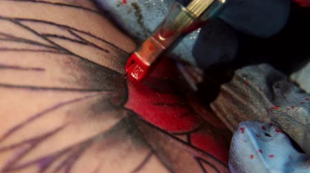kár : Needle tattoo machines inject a red ink into the skin of a man. Tattoo art on body. Makes a tattoo. Professional tattooist doing tattooing in studio. Close-up.